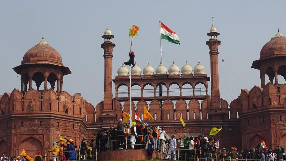 A man hangs on to pole holding a Sikh religious flag along with a farm union flag at the historic Red Fort monument during a protest in New Delhi, India, on January 26, 2021.