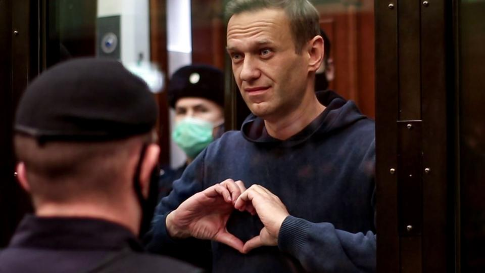 This screen grab shows Russian opposition leader Alexey Navalny gesturing a heart shape from inside a glass cell during a court hearing in Moscow on February 2, 2021.