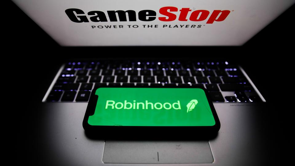Robinhood logo displayed on a phone screen and GameStop logo displayed on a laptop screen are seen in this illustration photo taken in Poland on January 31, 2021.