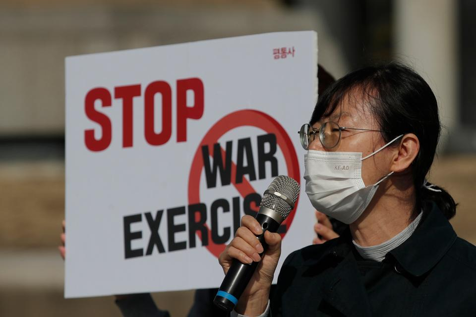 A South Korean protester speaks during a rally to oppose the joint military exercises between South Korea and the US near the presidential Blue House in Seoul, South Korea, March 8, 2021.