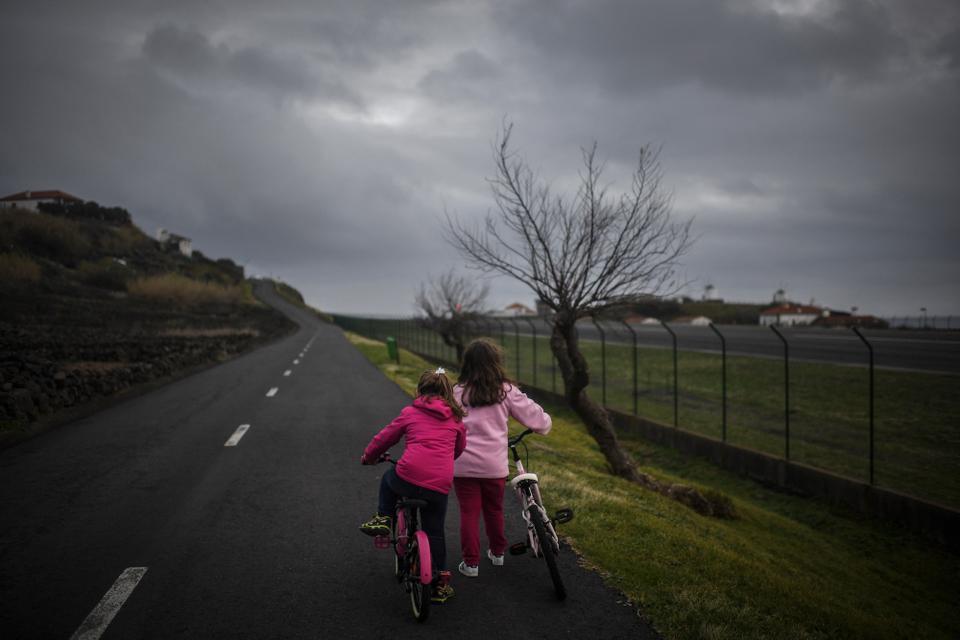 Duas mulheres andam de bicicleta na estrada com o aeroporto do Corvo, na Vila do Corvo, nos Açores, a 10 de março de 2021.