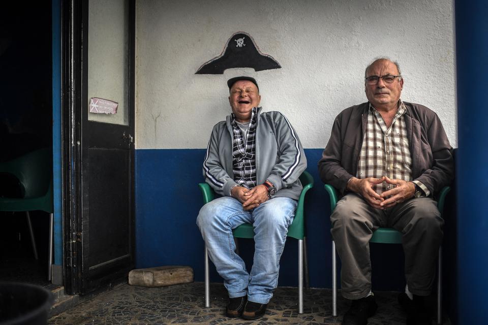 11 de março de 2021 Um velho sentado sob um chapéu de pirata pintado na parede de um bar na Ilha do Corvo, nos Açores