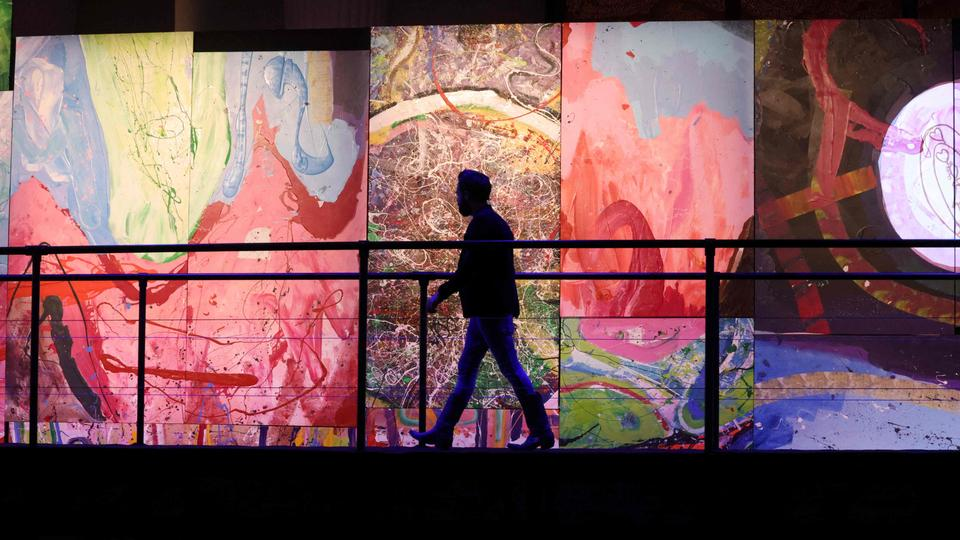 Dubai-based British contemporary British artist Sacha Jafri walks in front of fragments of his painting entitled 'The Journey of Humanity', in the Emirati city of Dubai, on February 25, 2021.