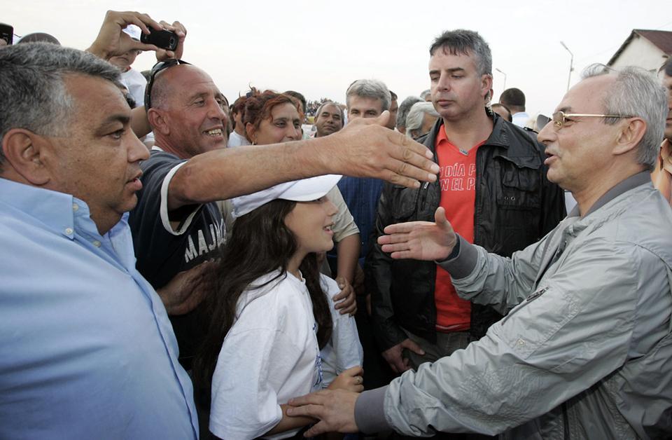 """Поддръжници на партията """"Движение за права и освобождение"""" (TPS) си стиснаха ръката на лидера на партията Ахмед Доган на 21 юни 2009 г. на предизборна кампания в българската столица София, източно от Басарджик."""