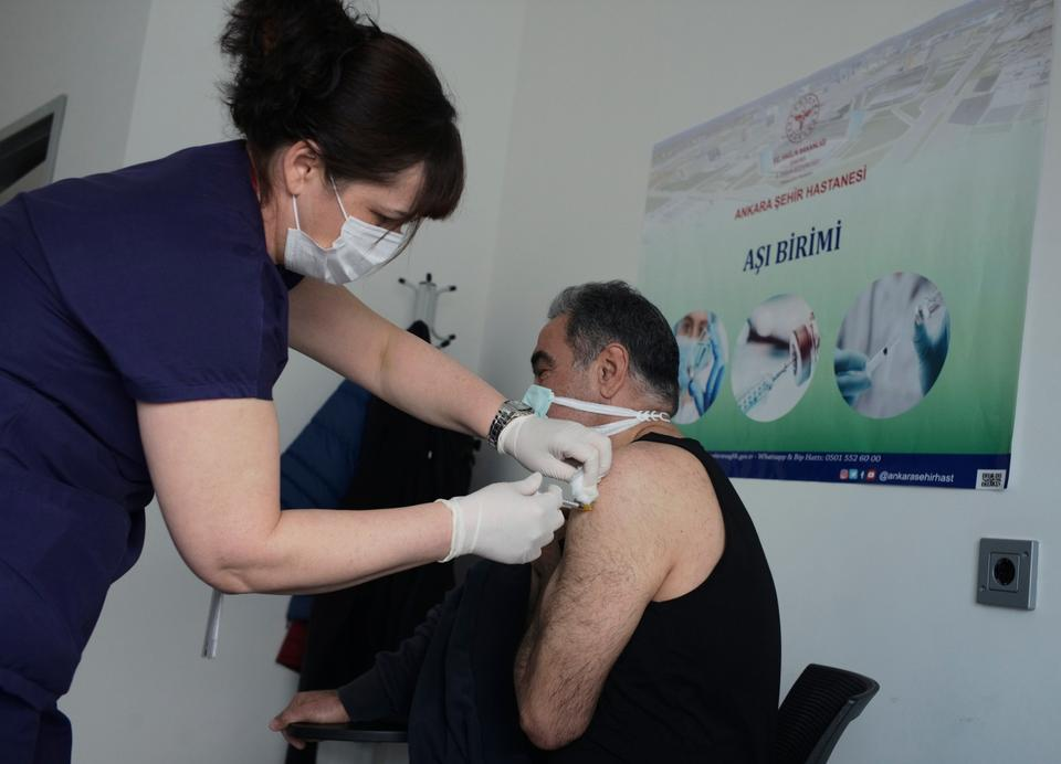 A nurse administers the Pfizer-BioNTech Covid-19 vaccine to a person at a hospital, in Ankara, Turkey, on April 3, 2021.