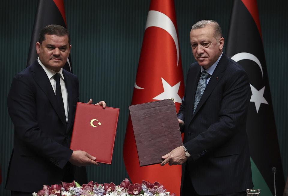 Ο Τούρκος πρόεδρος Ρετζέπ Ταγίπ Ερντογάν (δεξιά) και ο πρωθυπουργός της κυβέρνησης της Εθνικής Ενότητας της Λιβύης Αμπντ-Χαμίντ αλ-Νταμπάιμπα (αριστερά) απεικονίστηκαν κατά τη διάρκεια ανταλλαγής αρχείων μετά από την τελετή υπογραφής μεταξύ των δύο χωρών στο Προεδρικό Συγκρότημα στην Άγκυρα της Τουρκίας στις 12 Απριλίου 2021.