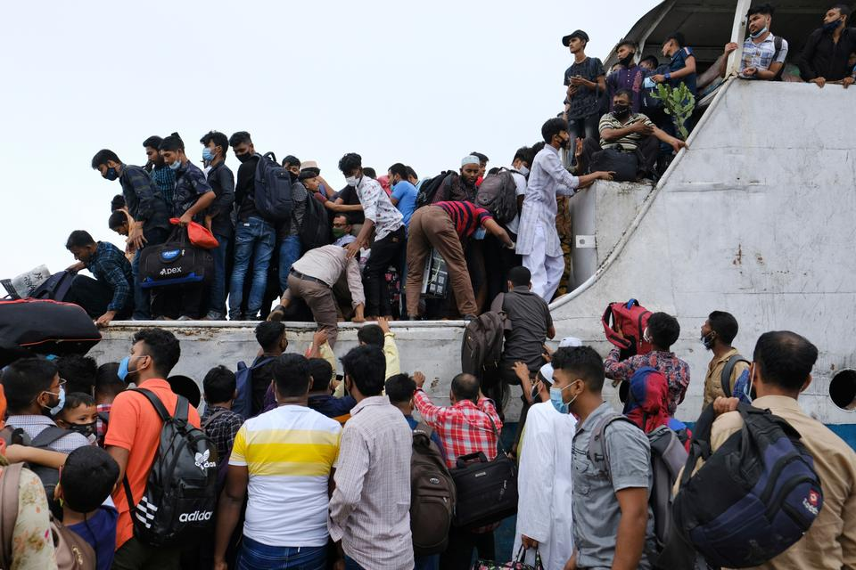 Thousands of people leaving for their native places to celebrate Eid-al-Fitr rush to the Mawa ferry terminal ignoring risks of coronavirus infection in Munshiganj, Bangladesh, Thursday, May 13, 2021.