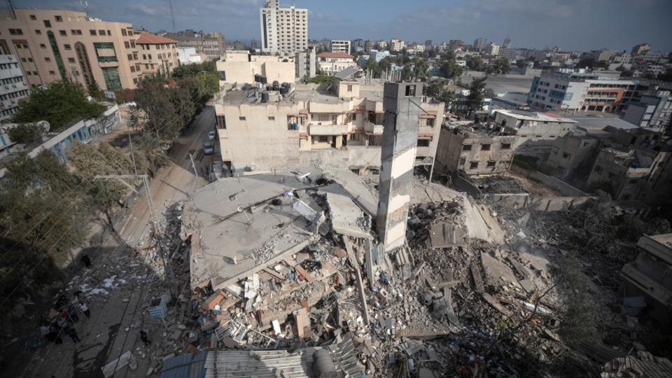 أعلاه ، بقايا مبنى مدني من ستة طوابق دمرته غارة جوية إسرائيلية على مدينة غزة في الساعات الأولى من عام 2021.  الثلاثاء 18 مايو.