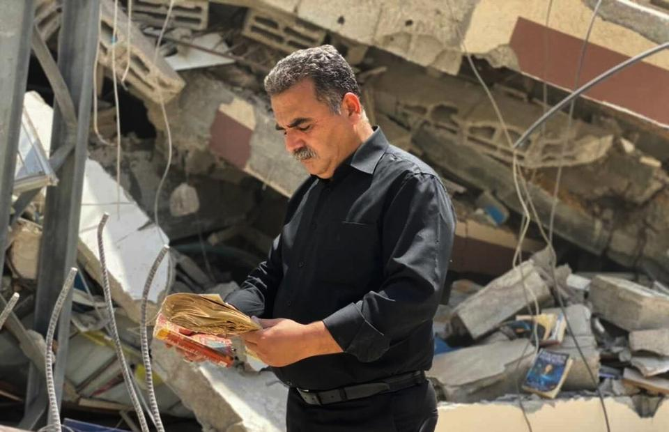Samir Mansour, the owner of the publishing house and bookstore that owns the largest collection of English literature in besieged Gaza looks at a book in front of the remains of his store that has been destroyed by Israeli air strikes. May 20. 2021, Gaza, Palestine.