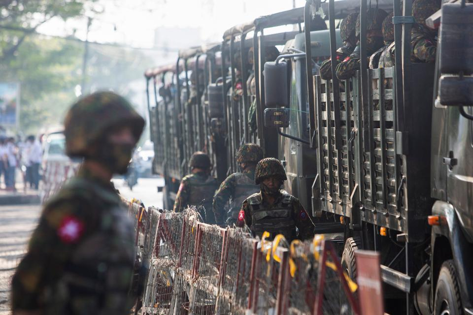 Soldiers stand next to military vehicles as people gather to protest against the military coup, in Yangon, Myanmar, February 15, 2021.