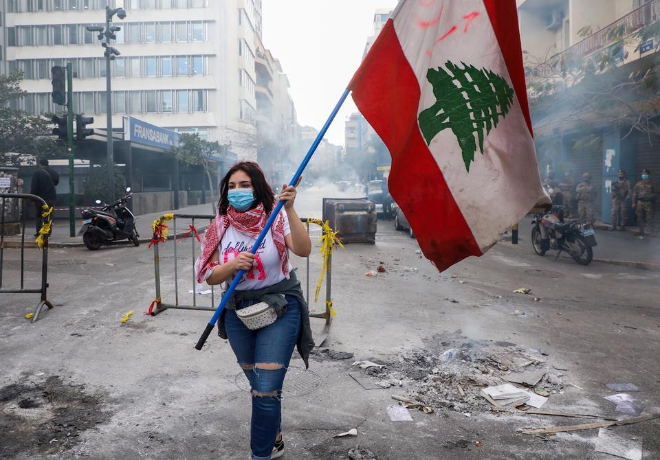 A demonstrator carries a national flag along a blocked road, during a protest against the fall in Lebanese pound currency and mounting economic hardships, near the Central Bank building, in Beirut, Lebanon March 16, 2021.