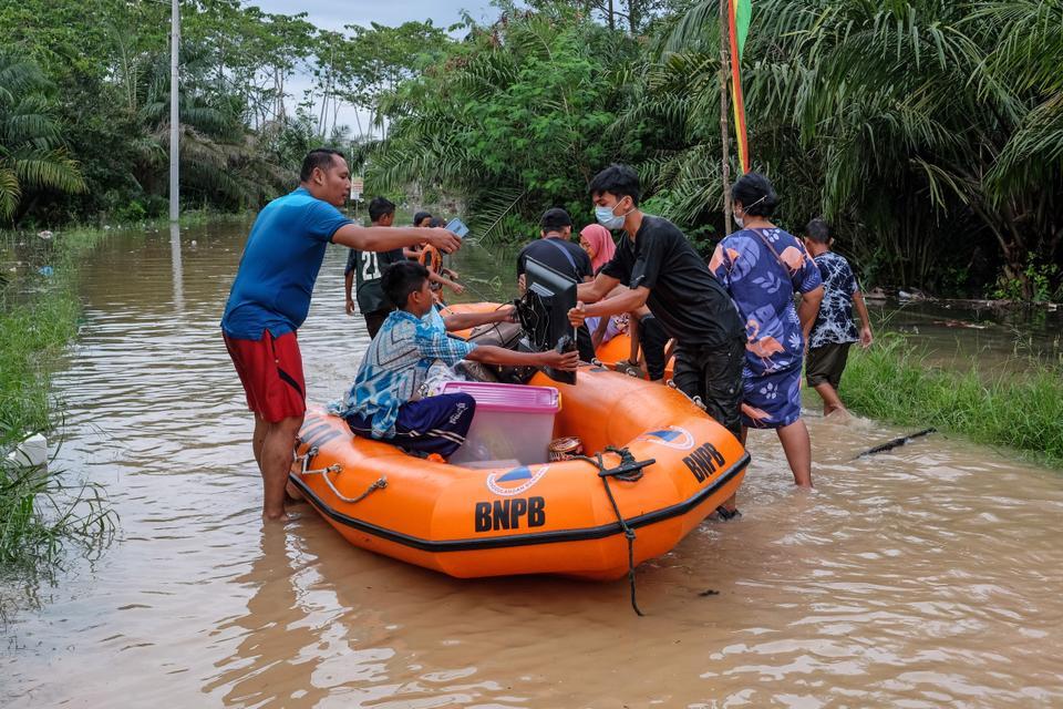 Warga berusaha mengevakuasi peralatan dari rumah yang terendam banjir akibat hujan deras dan meluapnya sungai di Bekanbaru, provinsi Rio, Indonesia pada 22 April 2021.