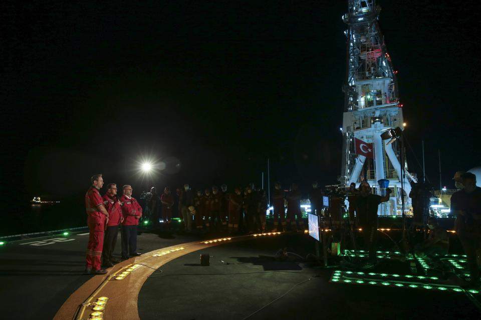 Energy and Natural Resources Minister Fatih Donmez (2nd L) stands on the deck of the Fatih drilling vessel as he attends the Sakarya gas field flaring ceremony in Zonguldak