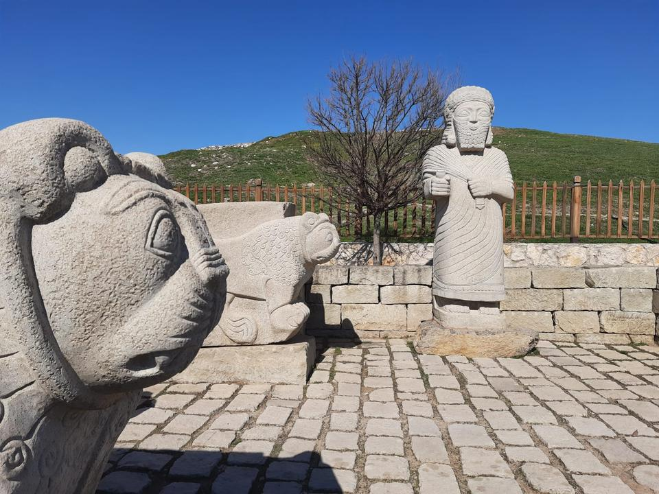 """Sculptures depicting a man and two lions at Arslantepe Mound (meaning """"Lion Hill"""" in Turkish)."""