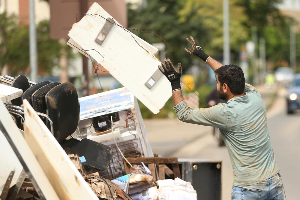A volunteer disposes of an electrical item, in a heap on the street, as the clean-up effort continues after flooding, in Euskirchen, Germany, Sunday, July 25, 2021.