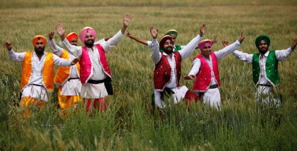 People in traditional attire perform the 'Bhangra', a Punjabi folk dance, as part of Baisakhi celebrations in a wheat field in Kokadwala village on the outskirts of Amritsar, India, Saturday, April 11, 2009.