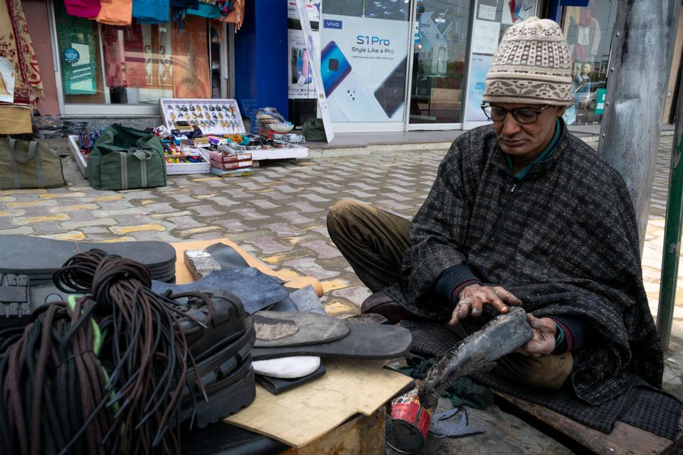 """Abdul Ahad Sheikh, 65, has worked as a cobbler for 17 years. Before that, Ahad was shot in 1994: """"I couldn't lift the hammer after that incident,'' he said. He was fired from various jobs, so he started working as a cobbler just like his father. """"I've been through hell all this time""""."""