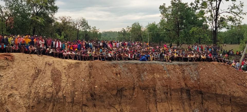 Villagers sitting on the other side of the trench that has been dug to make bridges crossing Silger Police Camp.