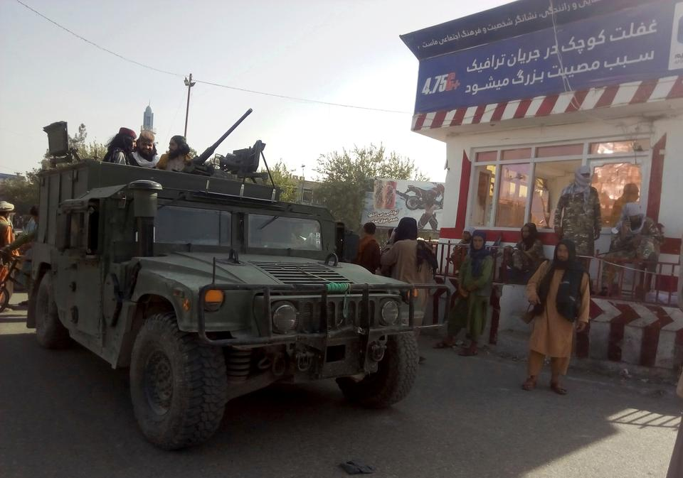 The Taliban began capturing Afghanistan's urban areas like Kunduz, signalling the movement's reach across the country. Taliban fighters stand guard at a checkpoint in Kunduz city, northern Afghanistan, Aug. 9, 2021.
