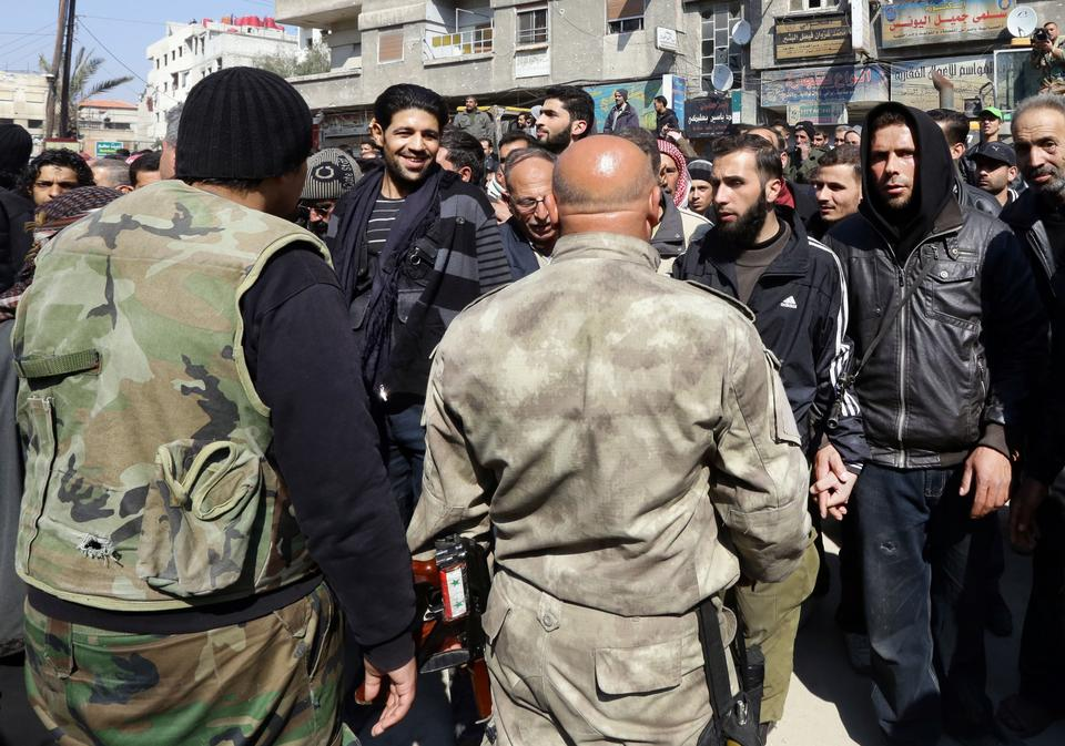 In this Feb. 17, 2014 photo, Syrian rebels, background, talk with Syrian regime forces, foreground, after a reconciliation agreement between the two groups, in Babila town southeast Damascus, Syria.