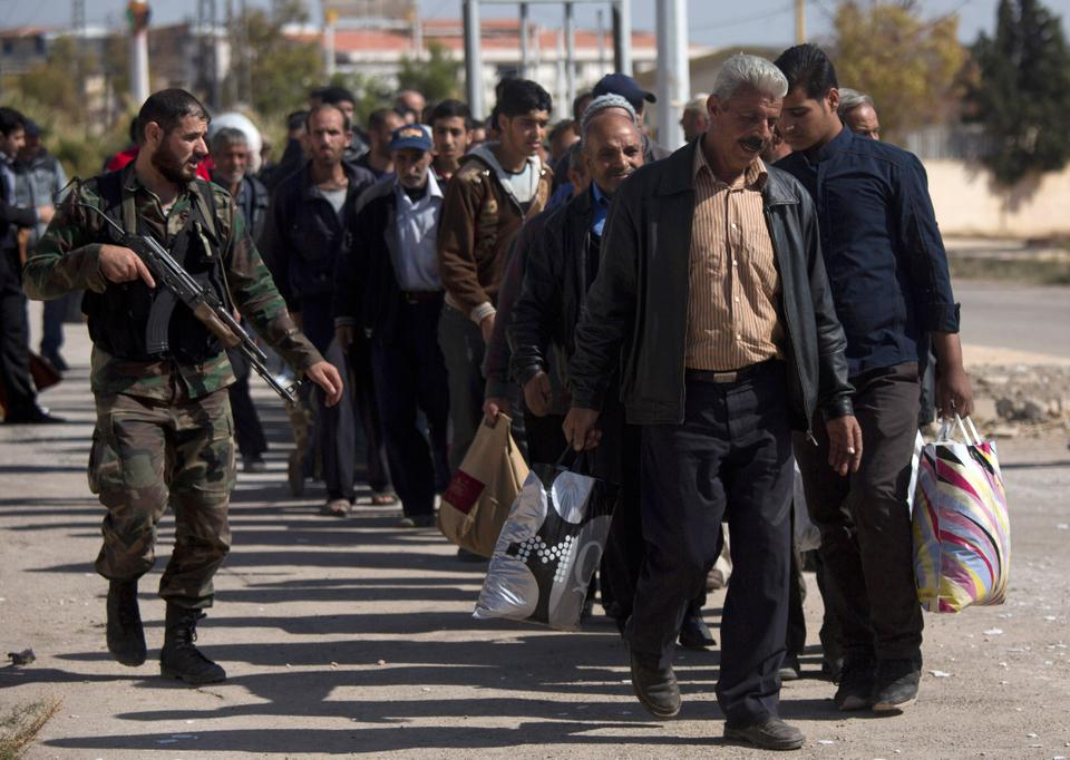 A Syrian soldier escorts men as they arrive from the rebel-held suburb of Moadamiyeh to regime-held territory on Oct. 29, 2013.