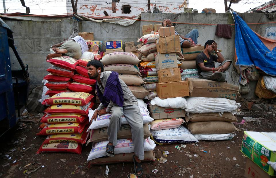In this Aug. 30, 2013 file photo, a laborer spits out tobacco as other rest on sacks of food grains at a wholesale market in New Delhi, India.