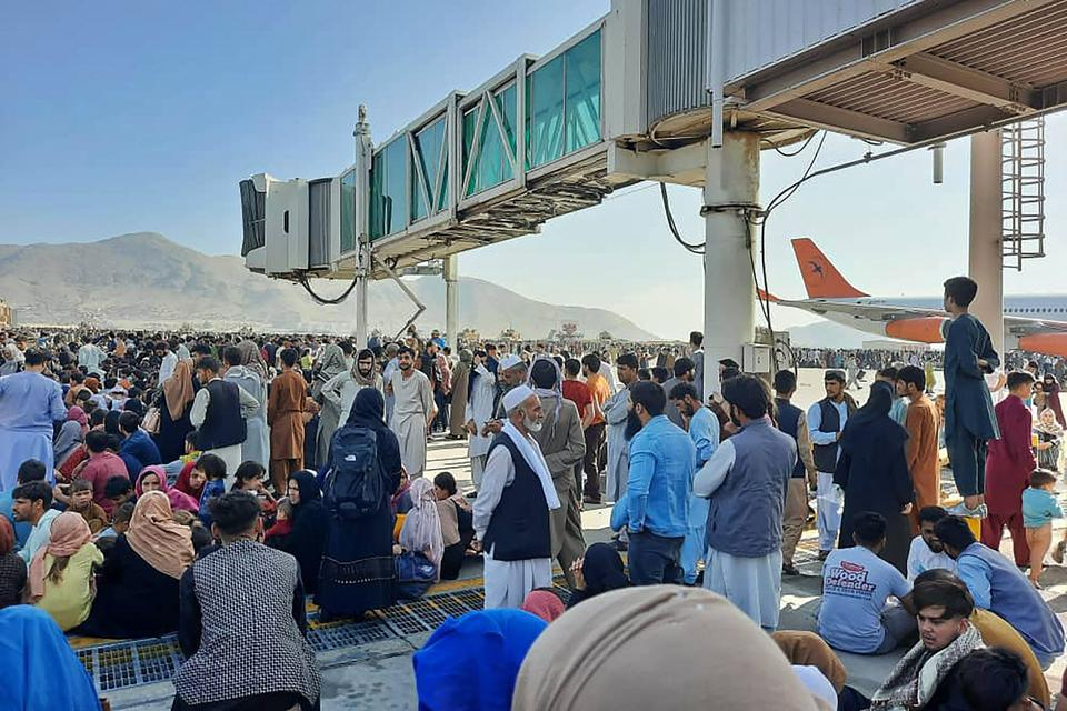 Afghans crowd at the tarmac of the Kabul airport on August 16, 2021, to flee the country as the Taliban were in control of Afghanistan.