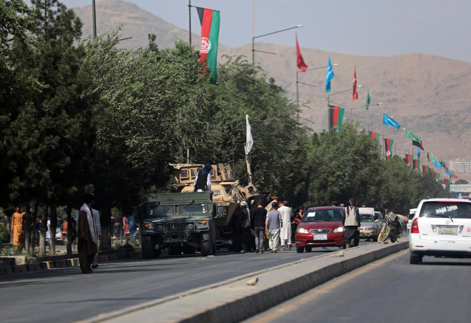The Taliban captured the Afghan capital without any fight after 20 years of losing power. Its fighters stand guard on the road leading to the Hamid Karzai International Airport, in Kabul, Afghanistan, Aug. 16, 2021.