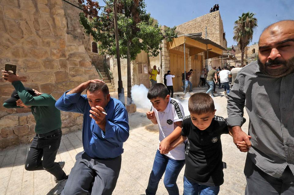 Palestinian worshippers speed away to avoid tear gas amid clashes with Israeli security forces, at a demonstration following the Friday prayers at the Ibrahimi mosque (Tomb of the Patriarchs) denouncing Israeli construction plans at the site, in the divided city of Hebron in the occupied West Bank on August 13, 2021.