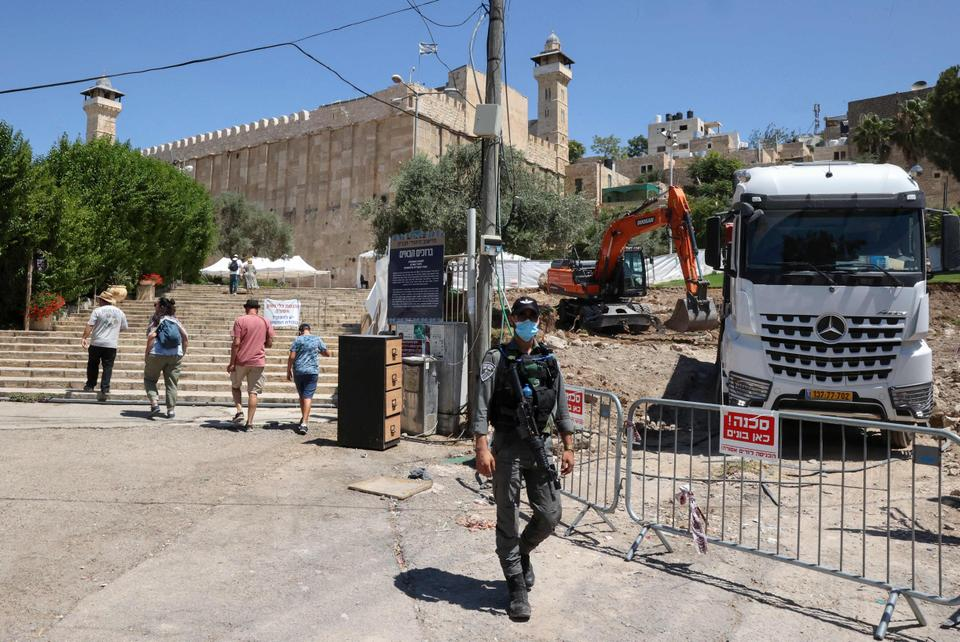 An Israeli security officer stands guard as an excavator digs amid construction works next to the Ibrahimi mosque (Tomb of the Patriarchs), in the divided city of Hebron in the Israeli-occupied West Bank on August 15, 2021. afp