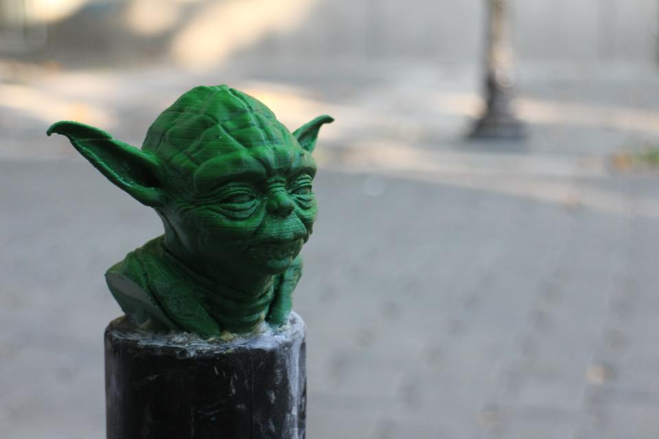 A 3D printed Yoda from Star Wars adorns a metal bollard, telling drivers to not there park.