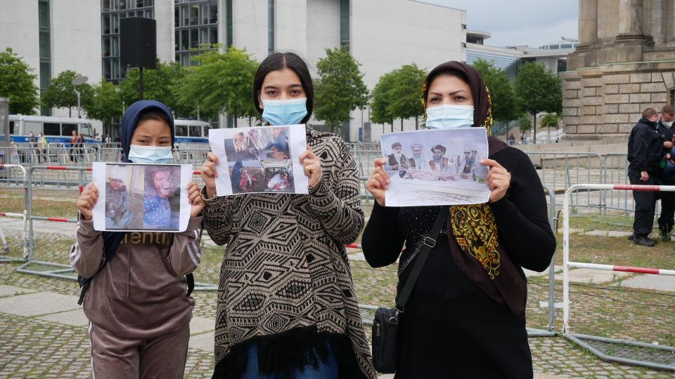 Elahe (in the middle) stands with her friend and mother, who have been living in Germany for six years after fleeing Afghanistan. They say they want the German government to help their country.