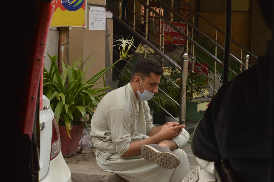 An Afghan refugee sitting on a shop perch in New Delhi.
