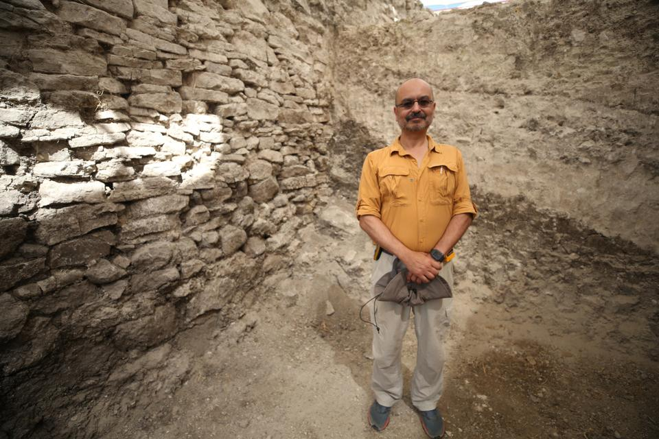 Dr Kaan Iren who is leading the excavation at Daskyleion poses in front of the Phrygian wall.