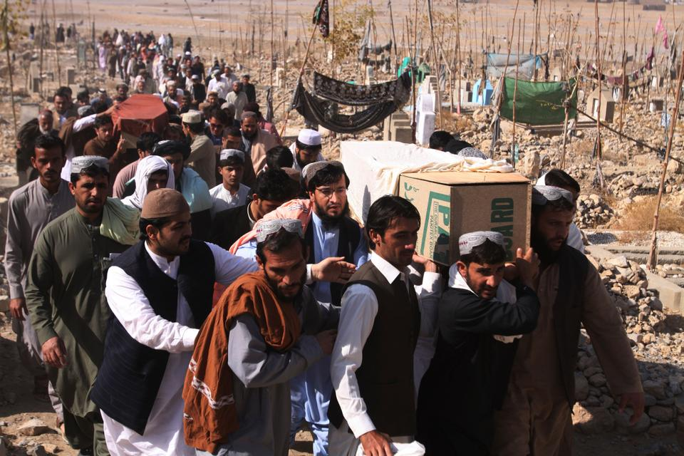 In this Saturday, Nov. 24, 2018 photo, people carry caskets of Pakistani civilians killed in a shootout during an attack on Chinese Consulate by militants in Karachi, in Quetta, Pakistan.