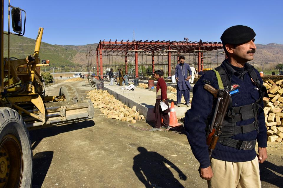 In this Dec. 22, 2017 file photo, a Pakistani police officer stands guard at the site of Pakistan China Silk Road in Haripur, Pakistan.