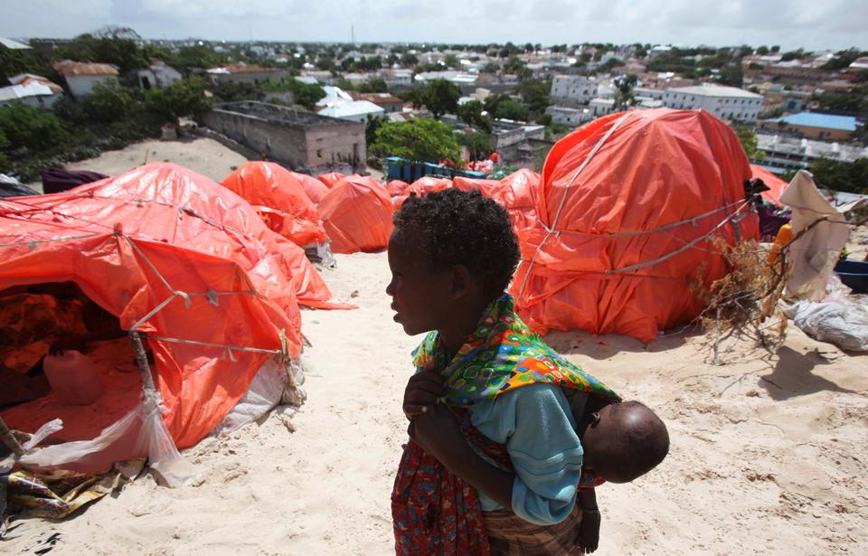 An internally displaced girl carries her sibling past makeshift shelter structures at the Gorgor camp in Somalia's capital Mogadishu, August 19, 2011.