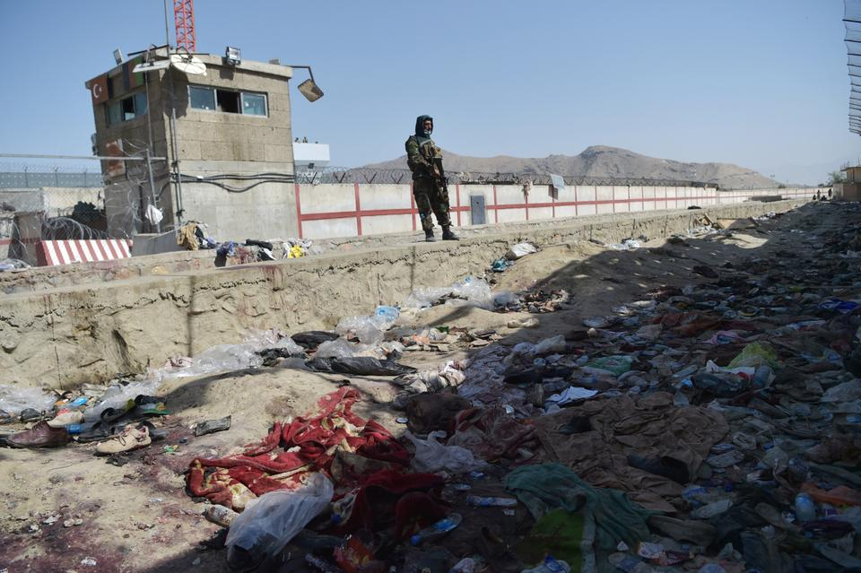 A Taliban fighter stands guard at the site of the August 26 twin suicide bombs, which killed scores of people including 13 US troops, at Kabul airport on August 27, 2021.