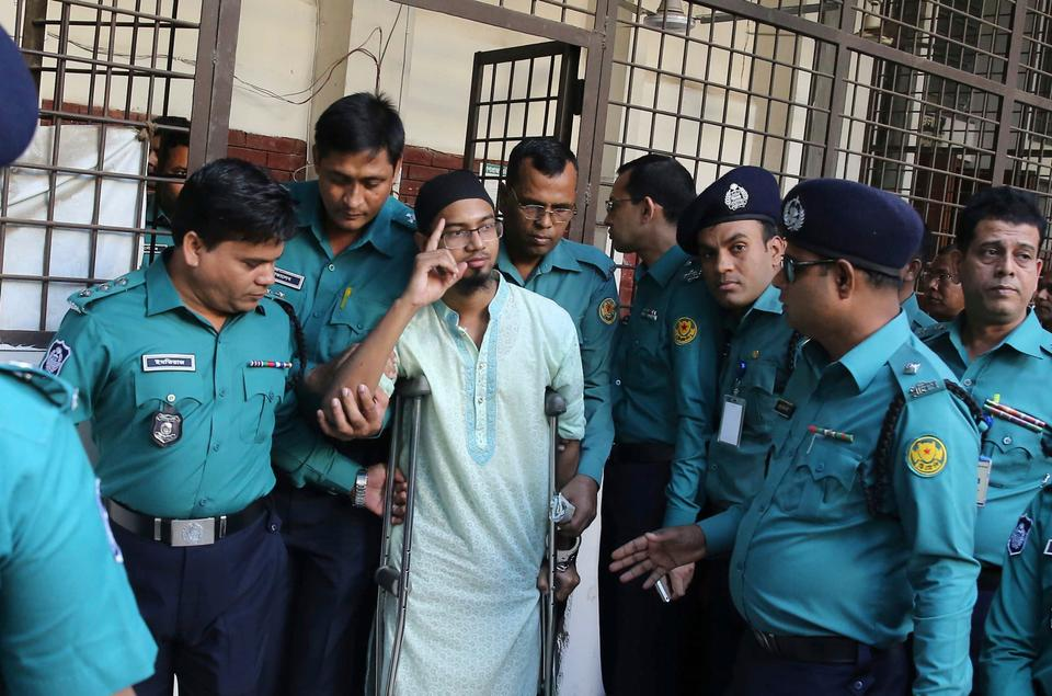 Police escort a member of a banned militant group after he was sentenced to death for an attack on a Dhaka cafe that killed more than 20 people in Dhaka, Bangladesh, Wednesday, Nov. 27, 2019.