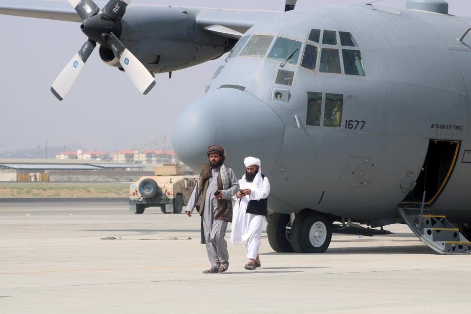 Taliban walk in front of a military airplane a day after the troops withdrawal from Hamid Karzai International Airport in Kabul