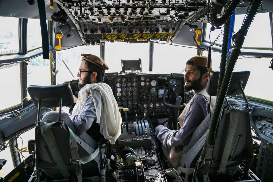Taliban fighters sit in the cockpit of an Afghan Air Force aircraft at the airport in Kabul