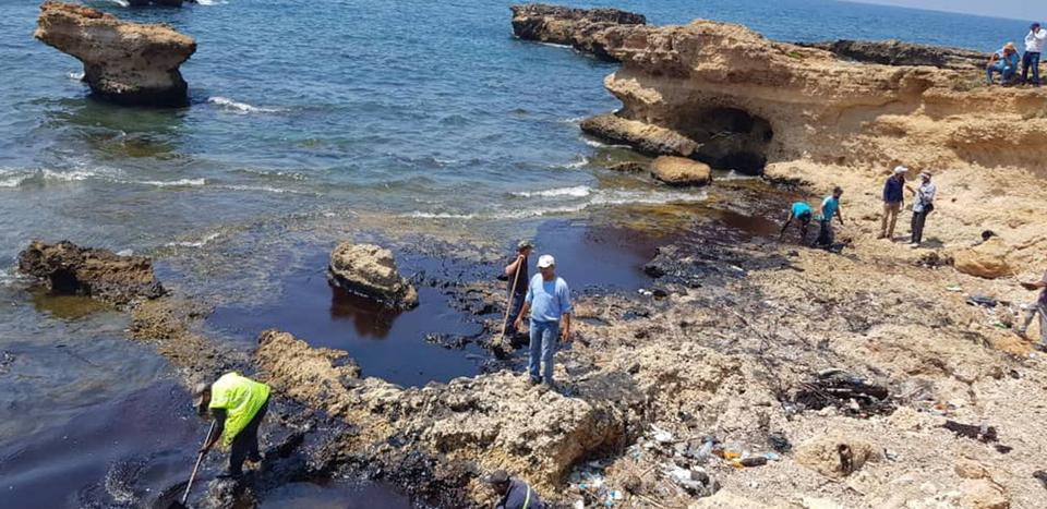 A handout picture released by the official Syrian Arab News Agency (SANA) on August 31, 2021 shows people cleaning Syria's Mediterranean coast following an oil leak from the Baniyas power plant.