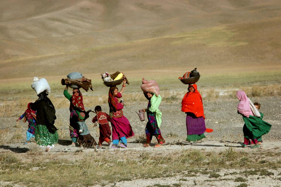 Hazara women walk to their homes at the end of the day in Bamiyan province, central Afghanistan, Aug. 26, 2005.