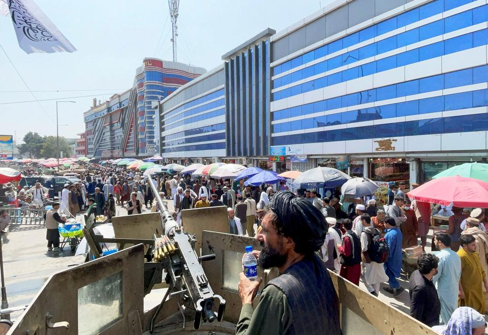 Members of Taliban security forces stand guard as crowds of people walk past in front of a money exchange market in Kabul