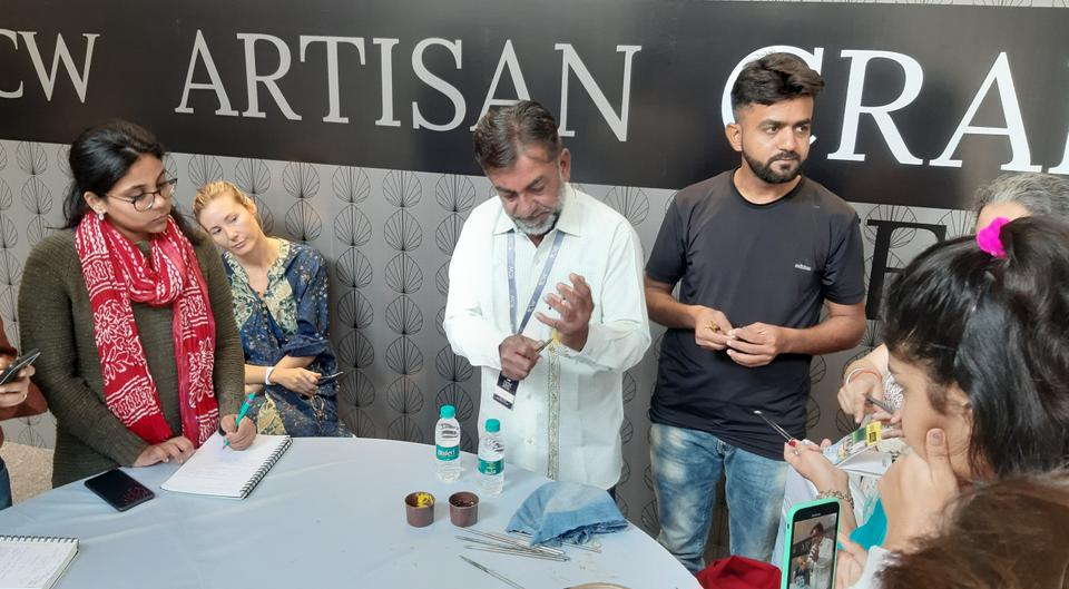Abdul Gafur Khatri performing Rogan painting at a convention. Next to him is his nephew M. Jabbar Arab Khatri. Both have been awarded as masters of the art.