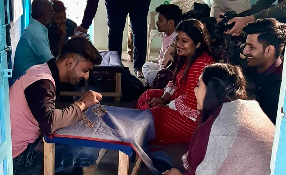 M. Jabbar Arab Khatri performing Rogan painting in front of students from India's National Institute of Fashion Technology. Behind him, in blue, is Abdul Gafur Khatri.