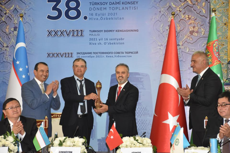 A scene from the 38th Term Meeting of TURKSOY's Permanent Council. Khiva Mayor Davletov is seen handing the symbolic trophy of the