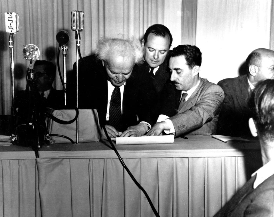 Israeli Prime Minister David Ben Gurion, left, signs a document in Tel Aviv, Palestine, proclaiming the new Jewish State of Israel in Tel Aviv at midnight on May 14, 1948. Witnessing the ceremony at right is Israel's first Foreign Minister Moshe Sharett, Zionist pioneer and leader in the establishment of the state of Israel. The man at center is not identified.