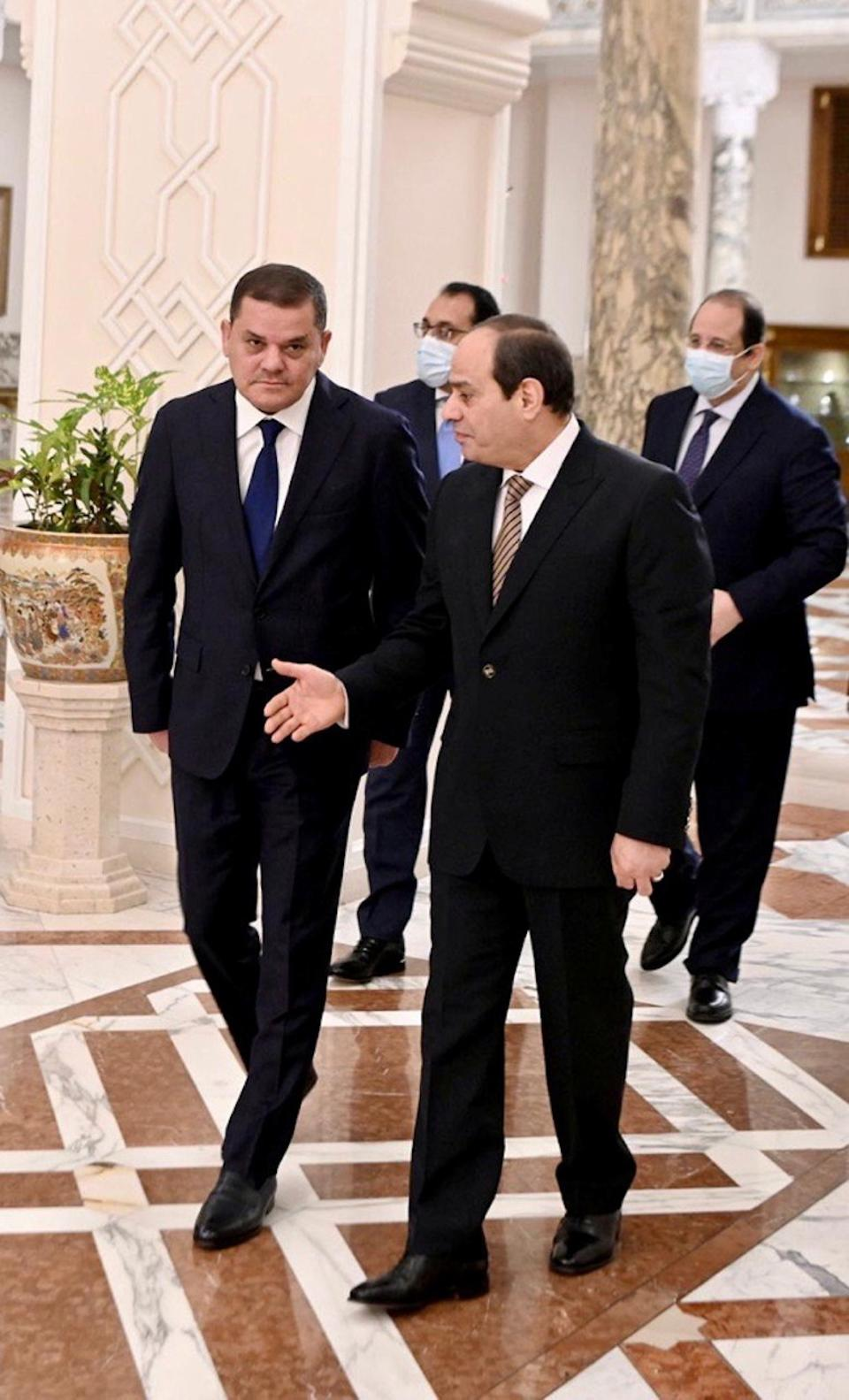 Libyan Prime Minister Abdulhamid Dbeibeh walks with Egypt's President Abdel Fattah al-Sisi during their meeting in at the Presidential Palace in Cairo, Egypt February 18, 2021.