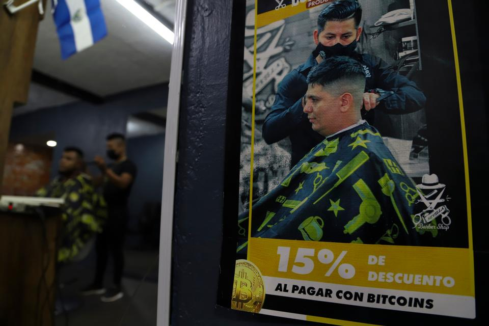 A poster inside Barber Shop announces discounts to those who pay with Bitcoin in Santa Tecla, El Salvador, Saturday, Sept. 4, 2021.  As of Sept. 7, all businesses must be able to accept payments in Bitcoin, except those lacking the technology to do so.